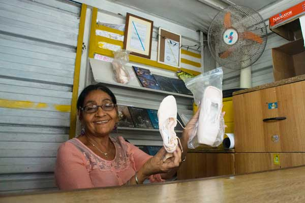 Mari Lu, a shoe vendor holds up a pair of pointe shoes