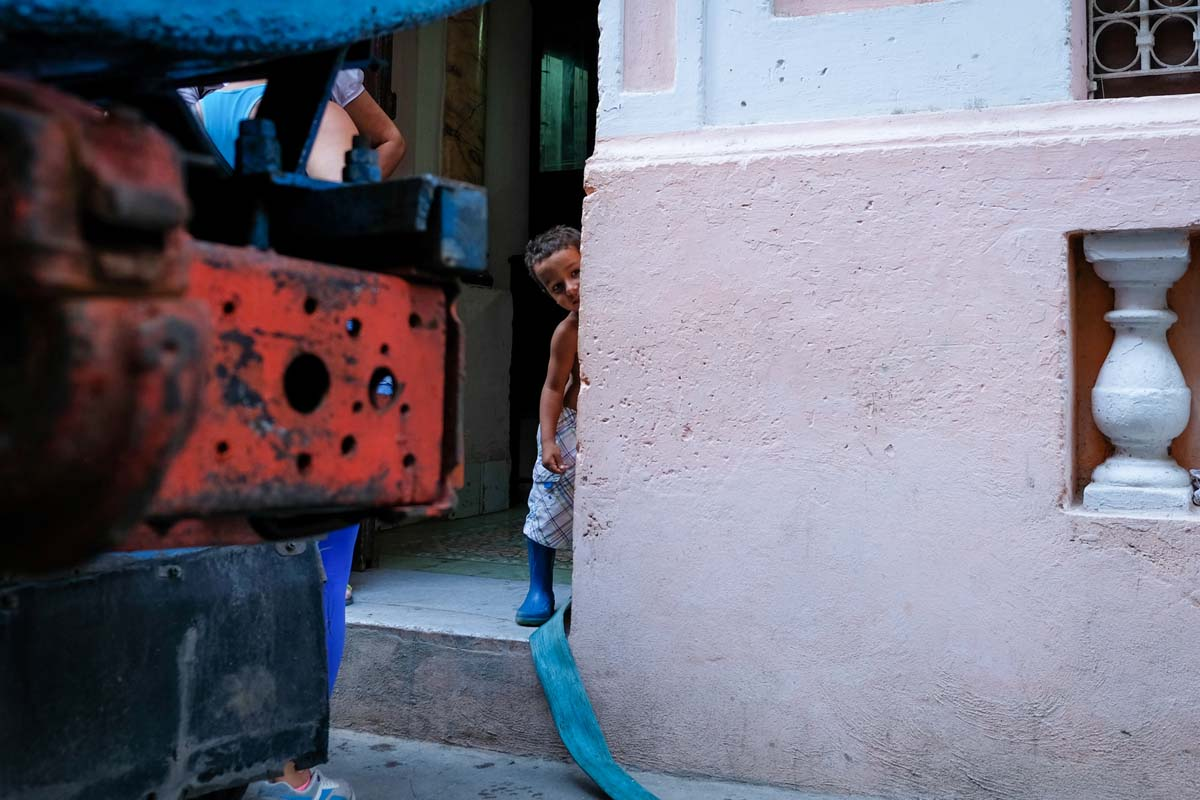 Alejandro hides among hoses